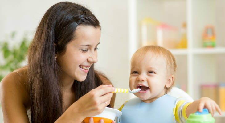 Photo of a woman smiling and spoon feeding a happy baby
