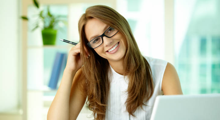 Photo of a woman wearing glasses holding a pen, head tilted to the side, smiling at the camera