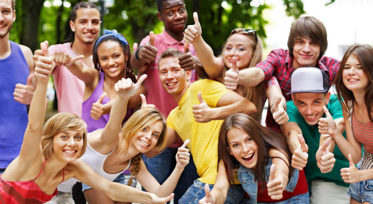 Photo of a group of young people with thumbs up smiling at the camera