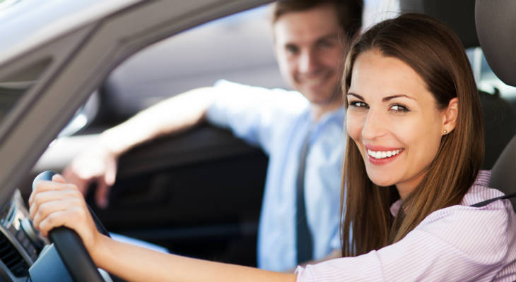 Photo of happy woman smiling behind the wheel of a car and a man smiling in the passenger seat in a blurred background