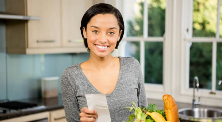Photo of a woman holding a receipt and a bag of groceries smiling at the camera