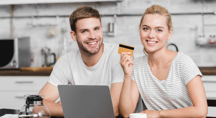 Photo of man and woman sitting behind a laptop holding a credit card smiling at the camera