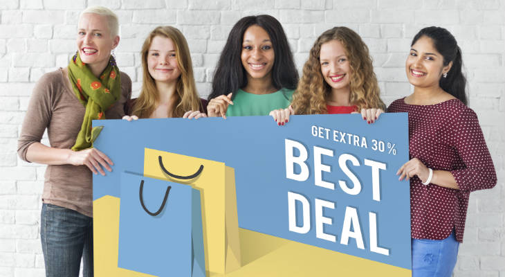Photo of a group of women holding a Best Deal sign, standing and smiling at the camera