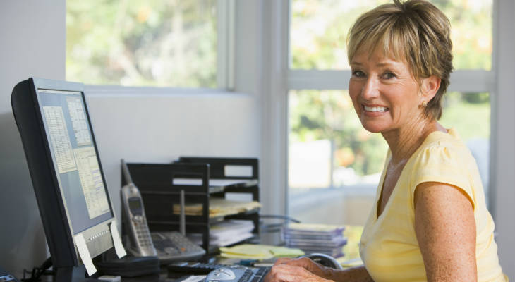 Photo of a woman typing on a keyboard smiling at the camera