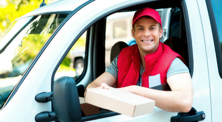 Photo of happy delivery driver in a vehicle holding out a package