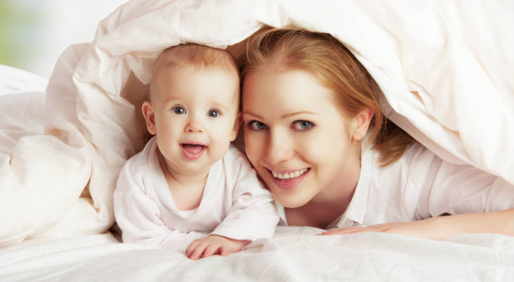 Photo of a woman and a baby lying under a blanket both smiling at the camera