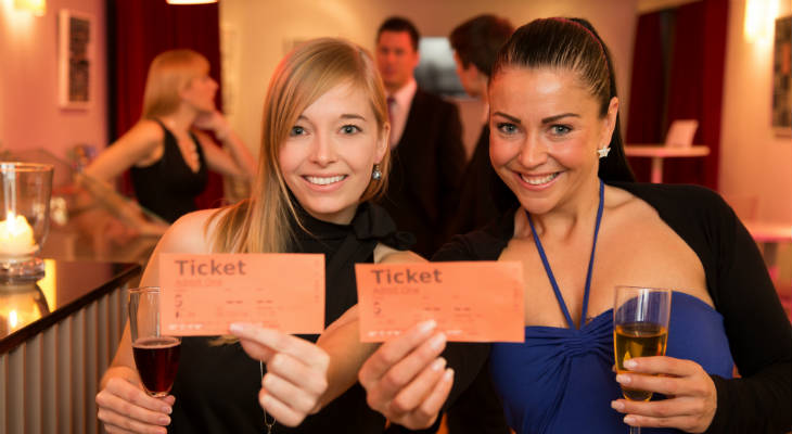 Photo of two women smiling and holding tickets