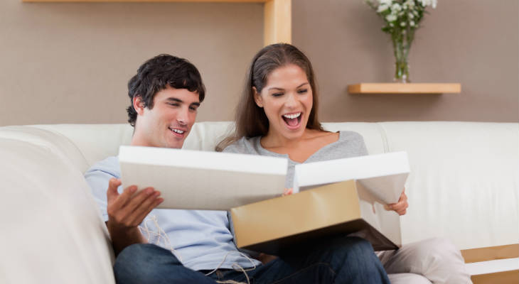 Photo of happy couple sitting on couch opening a box and looking surprised