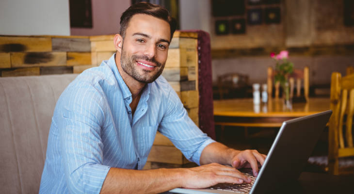 Photo of a man in a striped light blue shirt sitting with a laptop in a cafe similing at the camera