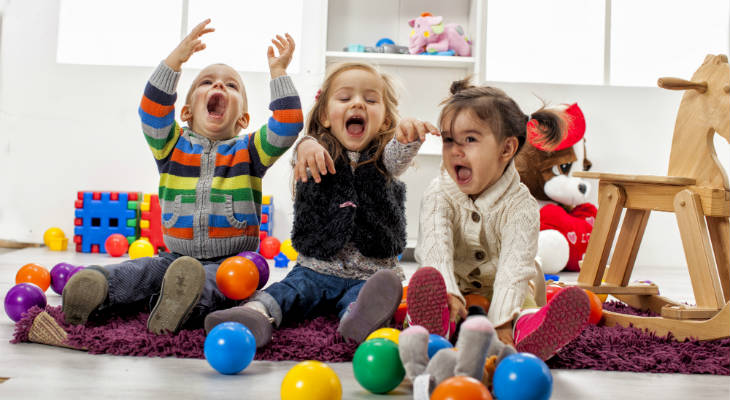 Photo of three excited kids playing with toys with their hands up in the air and mouth open