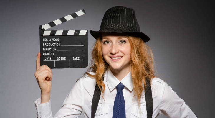 Photo of a woman dressed smartly wearing a hat holding a clapboard similing at the camera