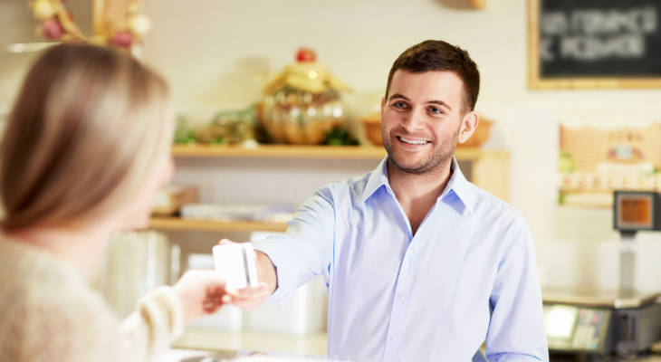 Photo of man smiling and serving a woman in a store