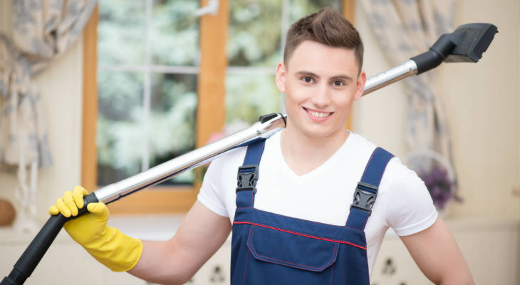 Photo of a man standing hold a vacuum cleaner smiling at the camera