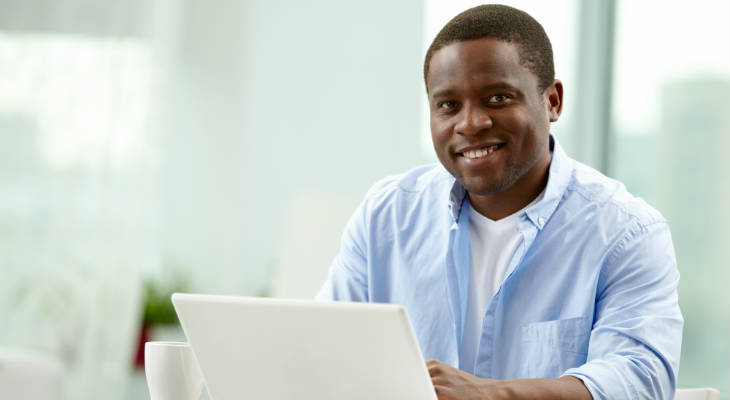 Photo of an African American man sitting behind a laptop computer smiling at the camera