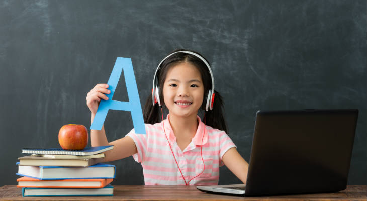 Photo of a girl wearing a headset, holding up a letter A, sitting behind a laptop computer, next to a pile of books with an Apple on top, smiling at the camera