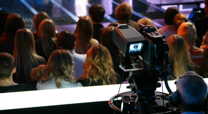 Photo of the back of a group of people sitting in front of a cameraman filming a TV show