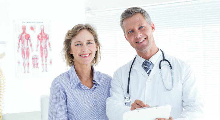 Photo of a male doctor and female patient smiling at the camera