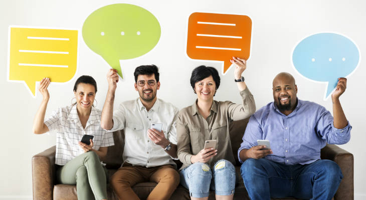 Photo of happy people sitting on couch holding up colorful speech bubbles