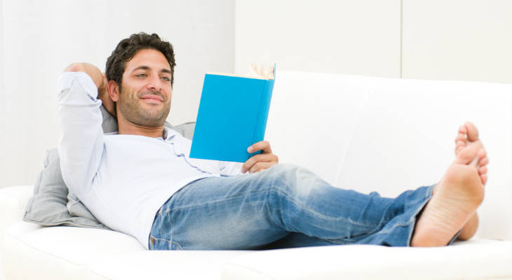 Photo of handsome man lying down on couch relaxing and reading