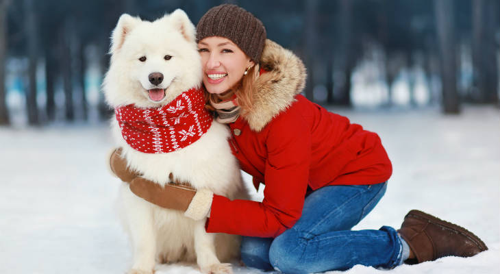Photo of a dog in a red scarf and a woman in a red jacket hugging the dog and smiling at the camera with snow on the ground and trees in the background