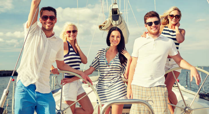 Photo of two guys and three girls standing on the deck of a sail boat, all smiling at the camera