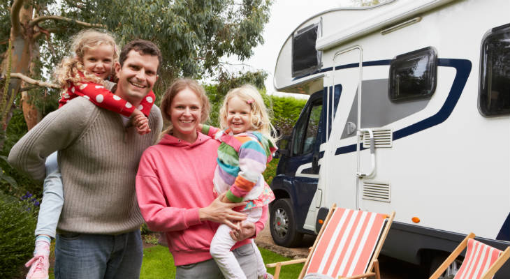 Photo of a family with two young girls standing in front of a RV, all smiling at the camera