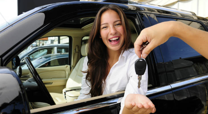 Photo of happy woman sitting in a vehicle smiling at the camera receiving a set of car keys