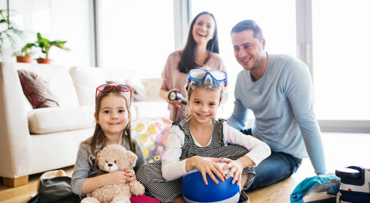 Photo of two youngs girls holding a teddy and beach ball, wearing goggles, sitting on the floor in front of their parents, smiling at the camera