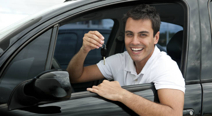 Photo of happy man sitting behind the wheel of a car holding up car keys smiling at the camera