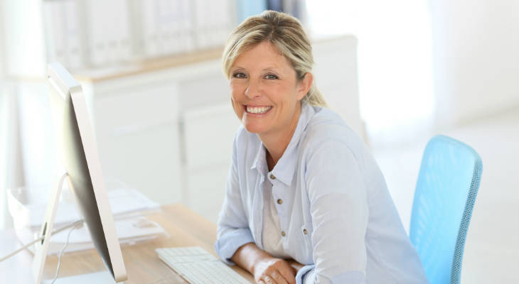 Photo of a woman sitting in front of a computer smiling at the camera