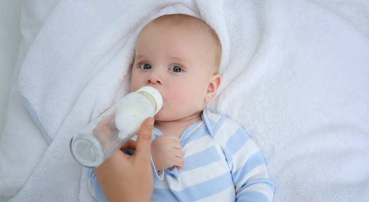 Photo of a baby lying on its back drinking a bottle of milk looking at the camera