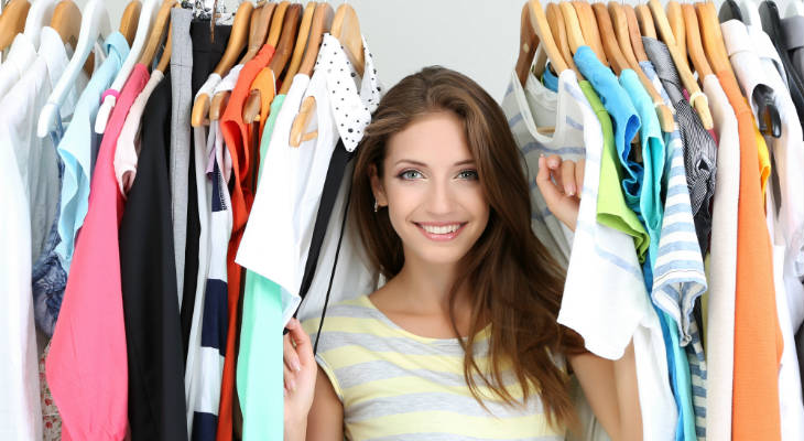 Photo of young woman standing under a rack of clothes smiling at the camera