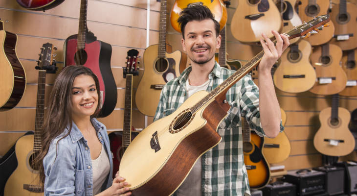 Photo of a man and a young woman standing in front of a guitar display, with the man holding a guitar and a young woman standing next to him, both smiling at the camera