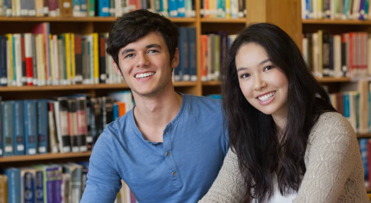 Photo of a male and female student sitting in front of bookshelves smiling at the camera