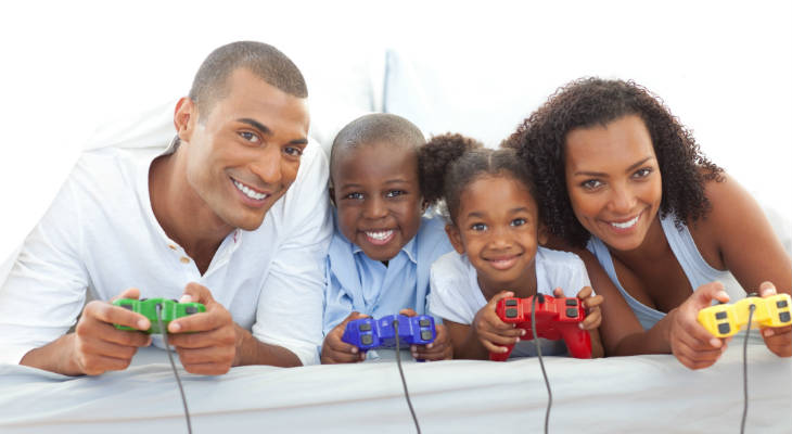 Photo of a family holding gaming controllers smiling at the camera