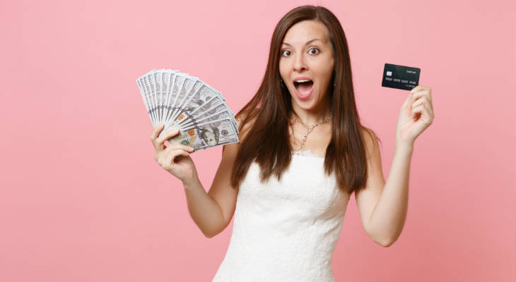 Photo of woman wearing a wedding dress, holding cash in one hand and a credit card in the other hand, looking at the camera mouth open looking surprised