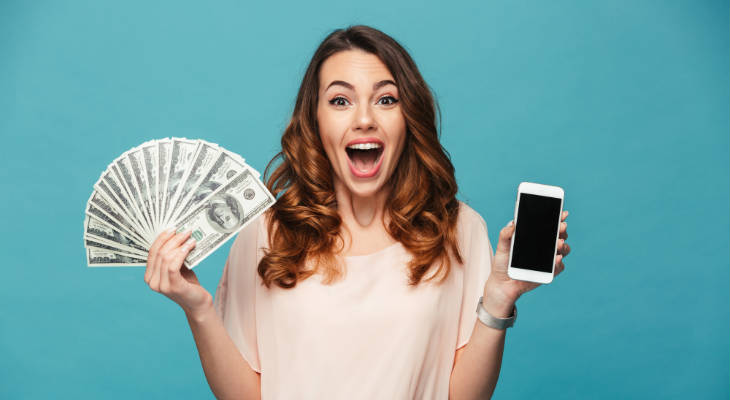 Photo of an excited woman holding a mobile phone in one hand and US dollar bills in the other