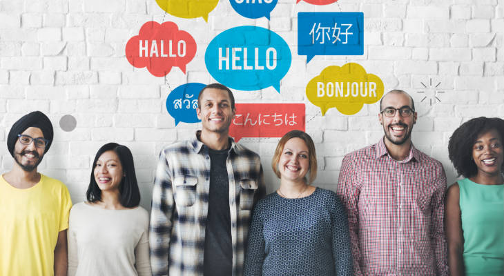 Photo of a group of men and women standing in front of a wall with foreign language concepts, all smiling at the camera