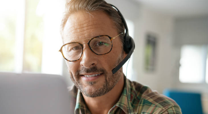 Photo of a man in glasses wearing a headset in front of a laptop computer smiling at the camera