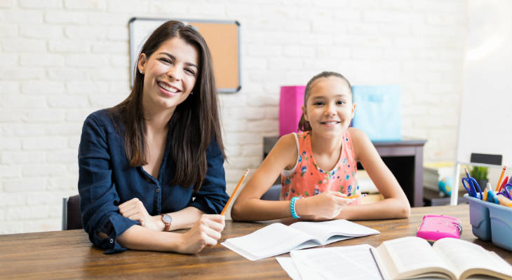 Photo of a woman tutoring a girl, both smiling at the camera