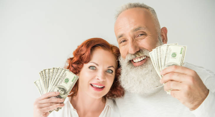 Photo of happy couple holding $100 bills smiling at the camera