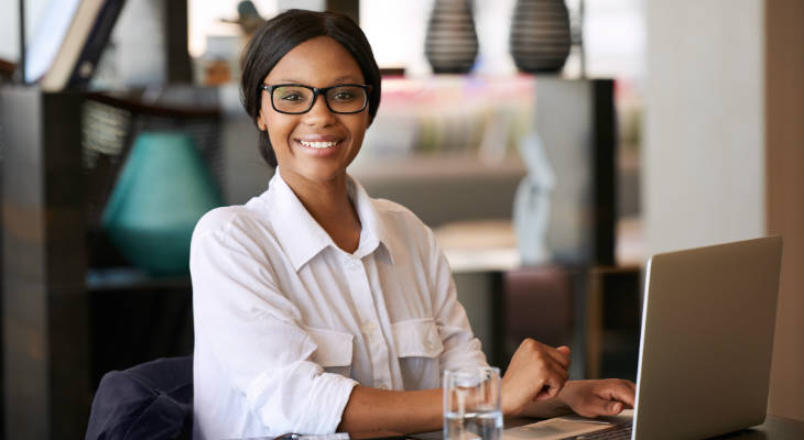 Photo of a woman wearing glasses sitting in front of a laptop similing at the camera