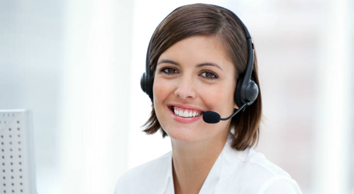 Photo of a woman wearing a headset with microphone similing at the camera